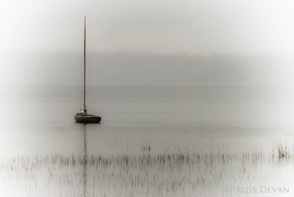 Sailboat at anchor in Maine during storm.