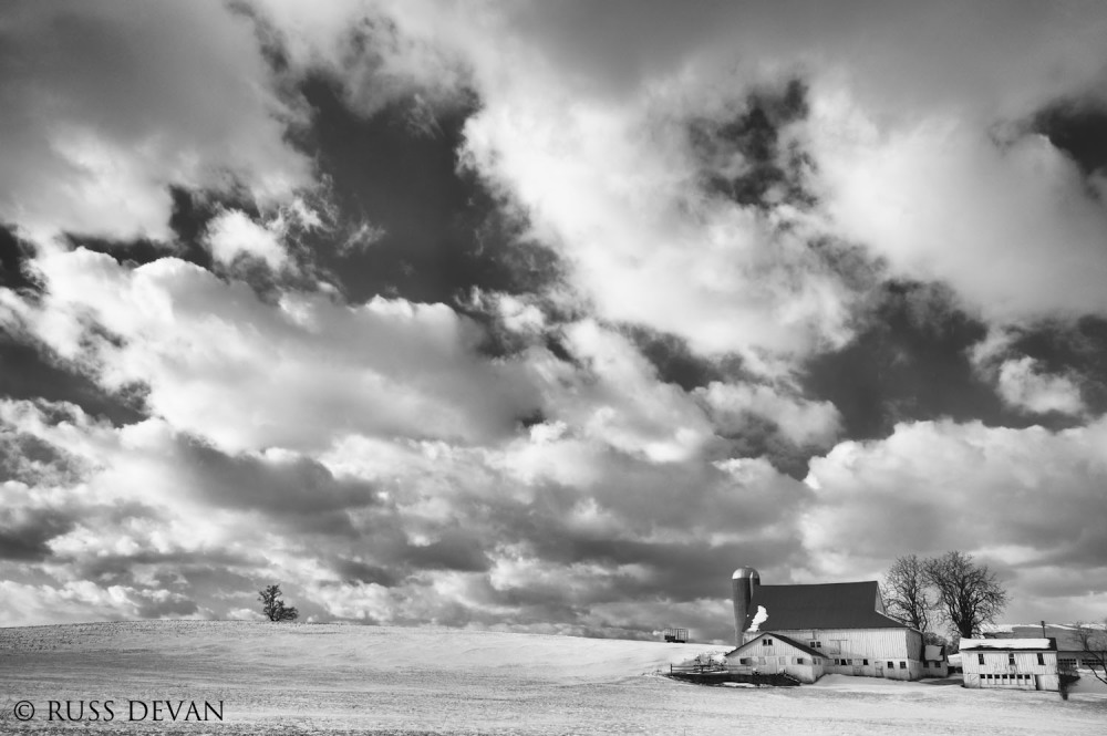 Snowy farm field and barn with dramatic cloudy sky
