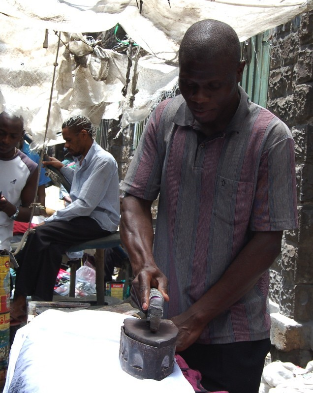 Man ironing a shirt for sale at Gikumba market