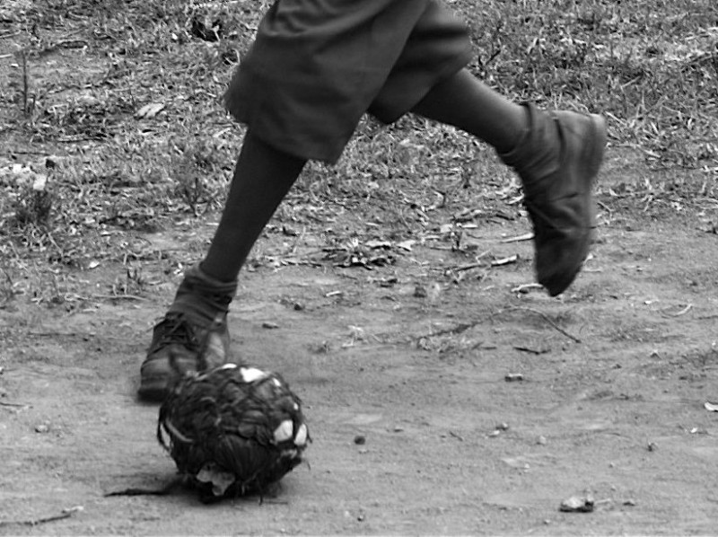 Boy playing soccer with a ball of plastic bags