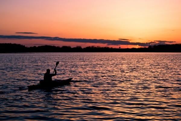 Jodi kayaking into the sunset