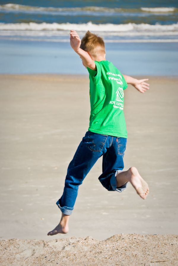 Ethan leaps off the sand cliff