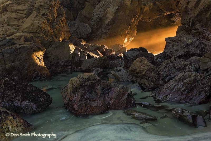 Sunset light through sea arch, Big Sur, California