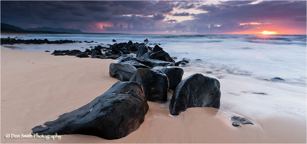 Sunrise on east facing beach with lava, Kauai.