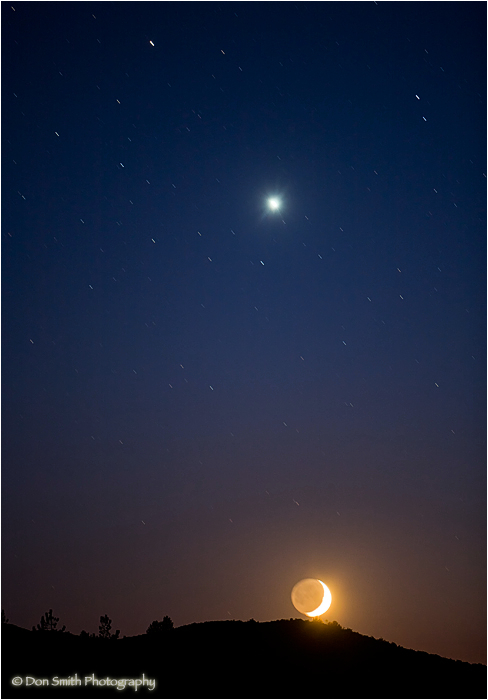 Crescent moonset with venus in night sky.