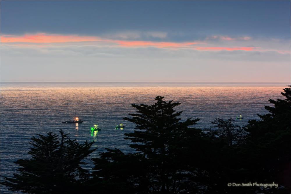 Fishing boats along Big Sur coast at dusk.