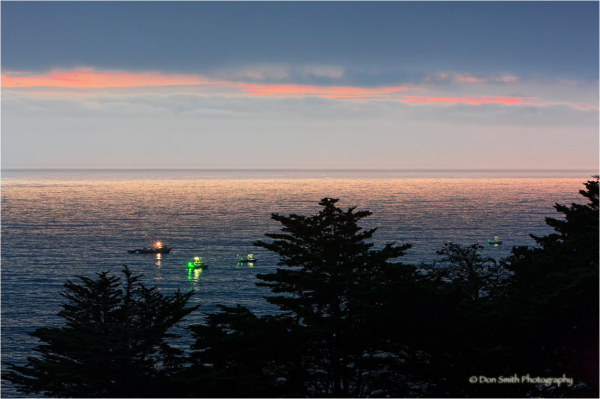 Fishing boats along Big Sur coast at dusk.