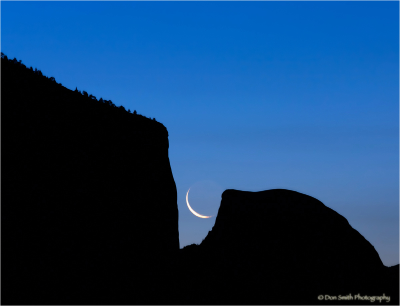 A crescent moon between El Capitan and Half Dome.