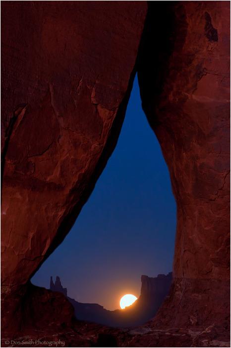 Full moon through Teardrop Arch, Monument Valley.