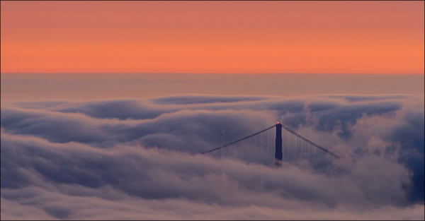 Dusk sky over fog and norht tower of Golden Gate.