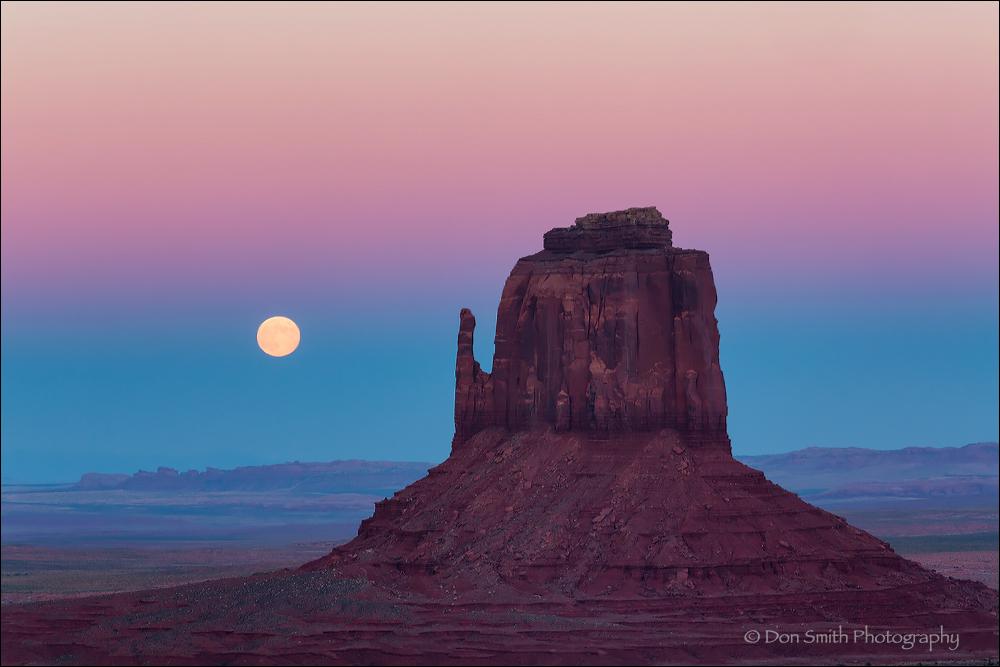 Full moon rising near east Mitten Monument Valley.