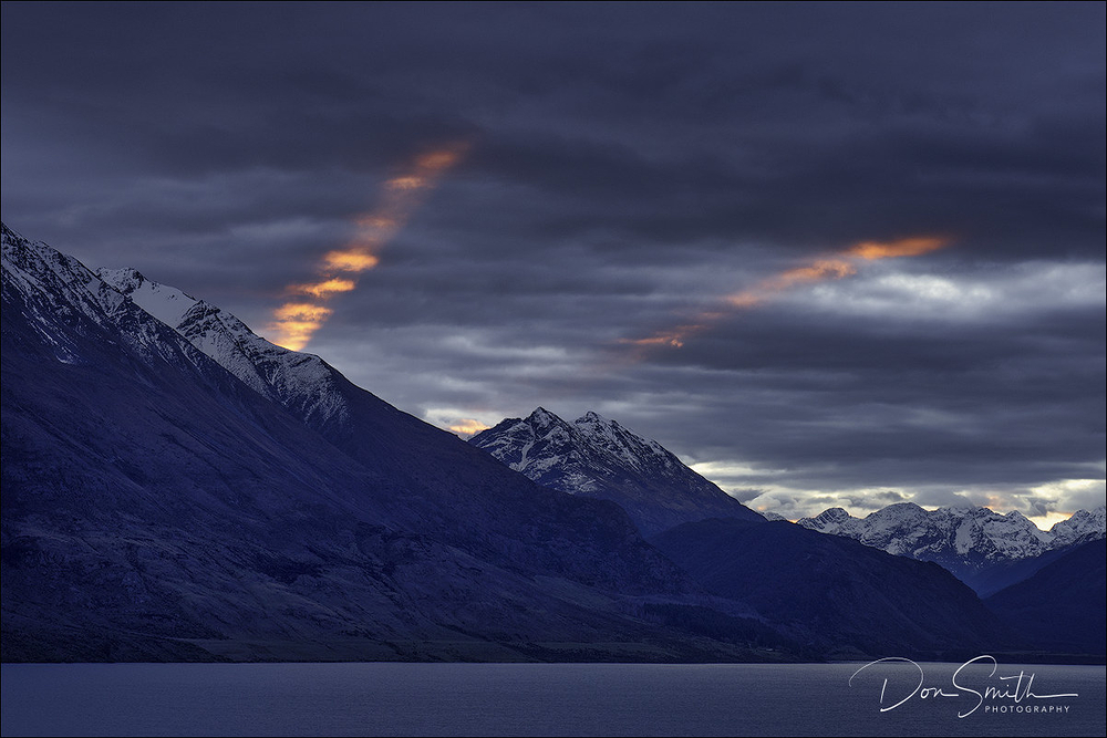 sun shafts over lake wakatipu, new zealand