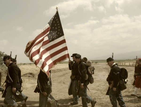Soldiers carry the flag off the battlefield