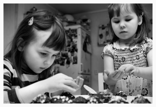 two girls decorating muffins