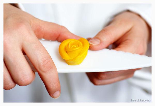 hands demonstrating handmade marzipan rose