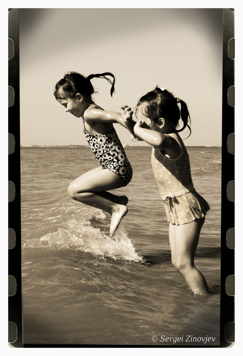 two girls jumping in water