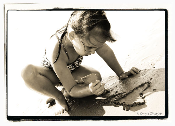 young girl drawing on sand