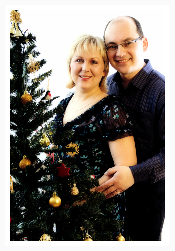 portrait of man and woman by the Christmas tree