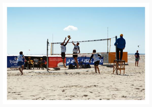 Men playing volleyball on the beach.