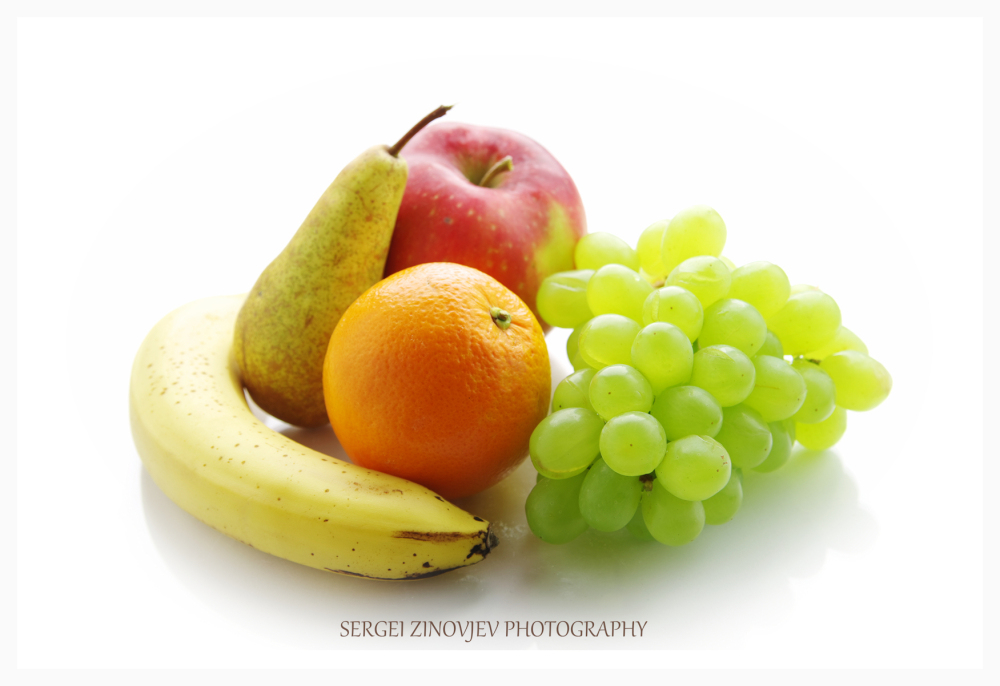 banana, pear, apple, orange and grapes on white
