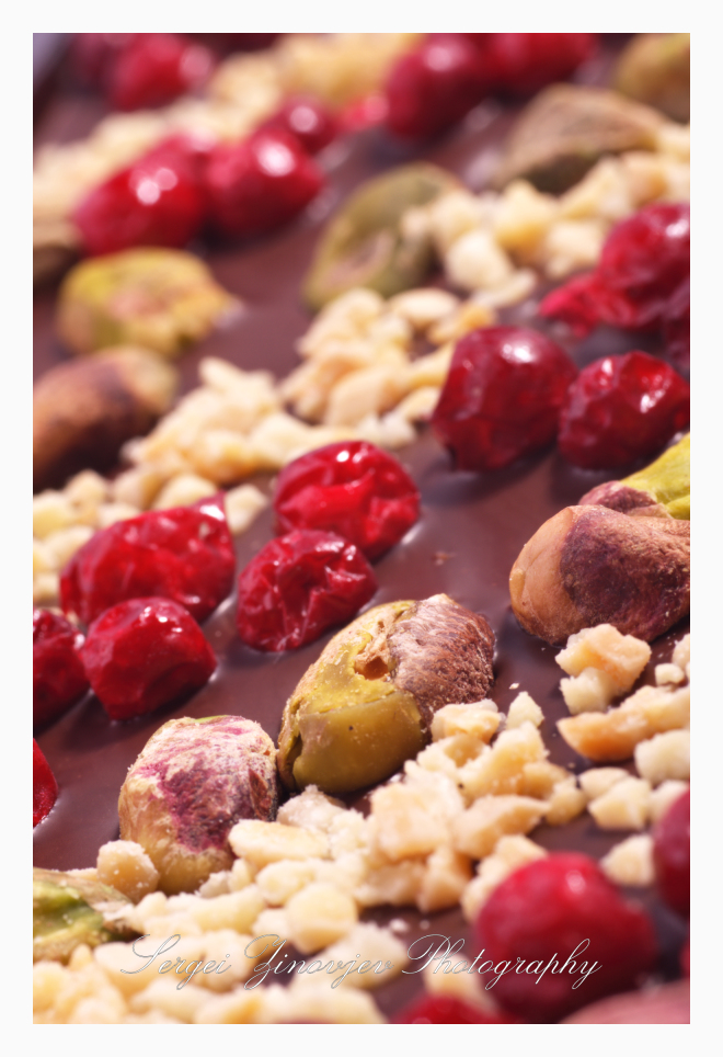 close-up of dark chocolate with nuts and berries
