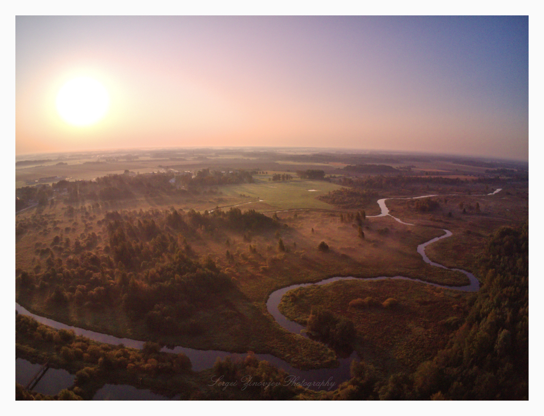 drone capture of sunrise over forest landscape