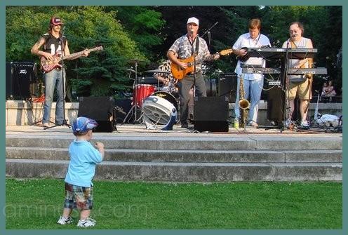 Boy watching daddy on stage playing mandolin