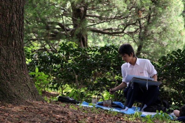 A young man doing art in the garden