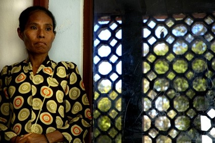 a woman watches her market stall in timor leste