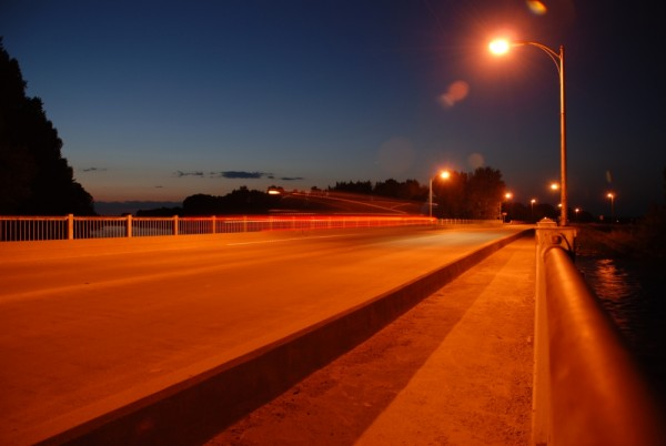 A car's tail lights trail over a deserted bridge.