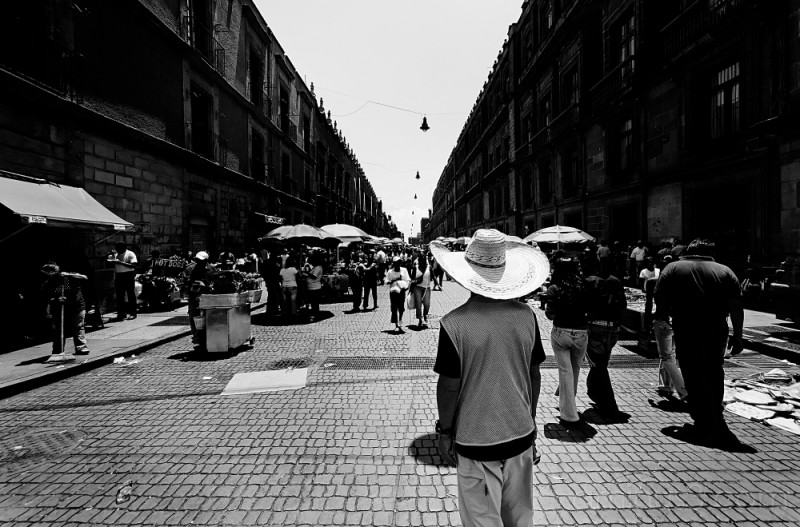 Man stands looking up Moneda Street, Mexico City.