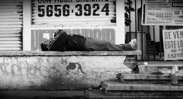 Man sleeps on street.