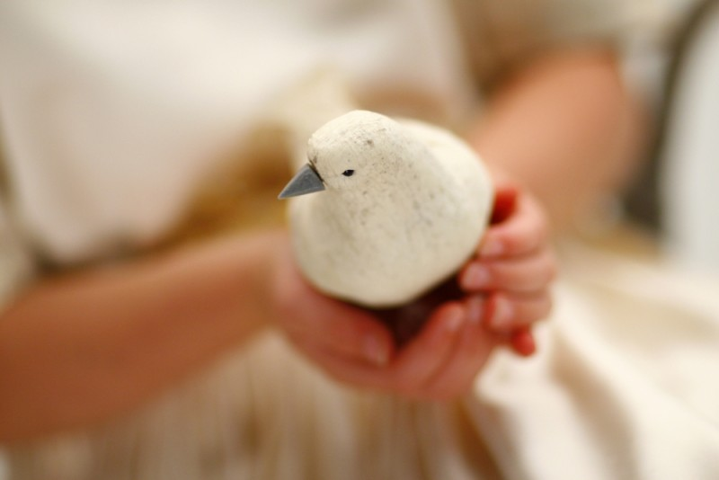 Young girl holding wooden bird