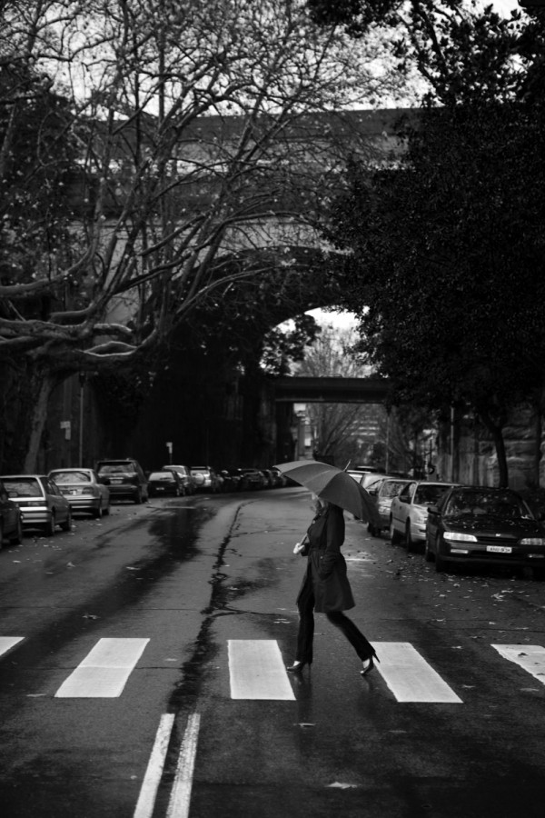 Woman crossing road on rainy day