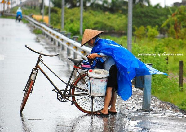 A lady with a bicycle in the rain