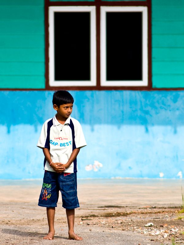 A boy standing in front of a house