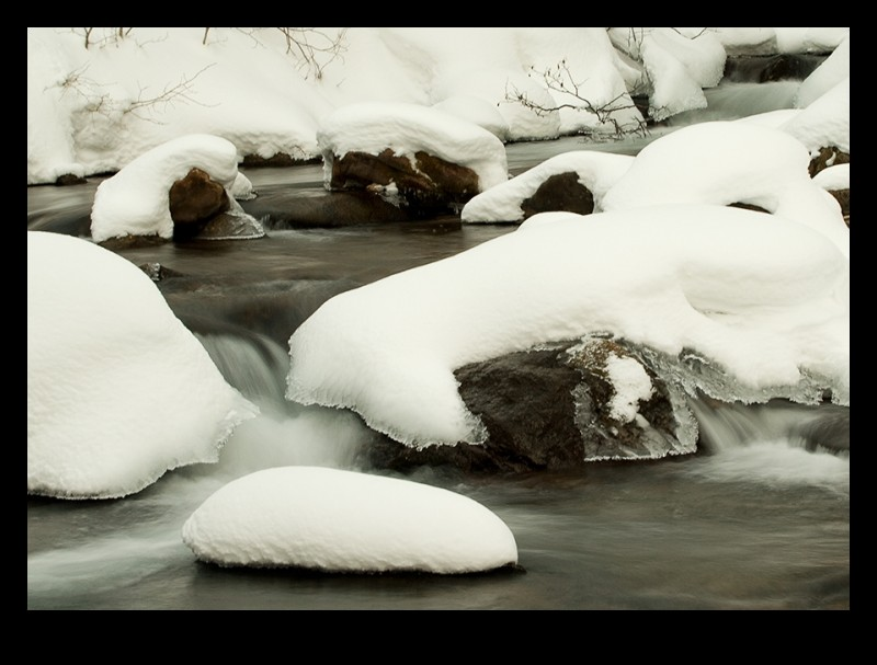 a flowing stream with ice and snow