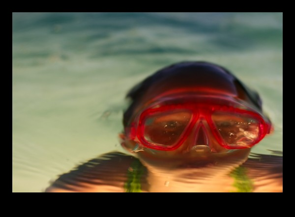 a girl with goggles coming out of the water
