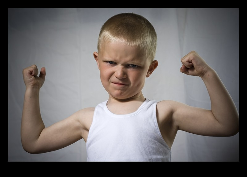 a young boy flexing his muscles