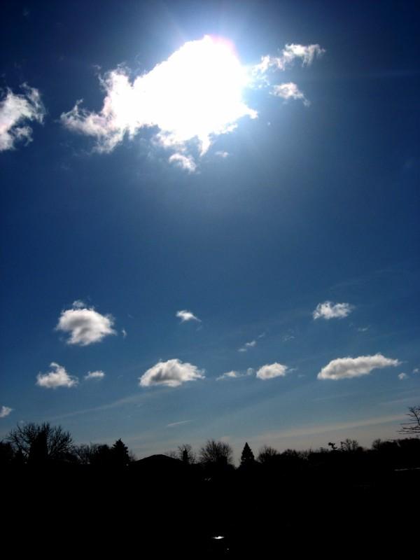 A shot of the sun behind a cloud
