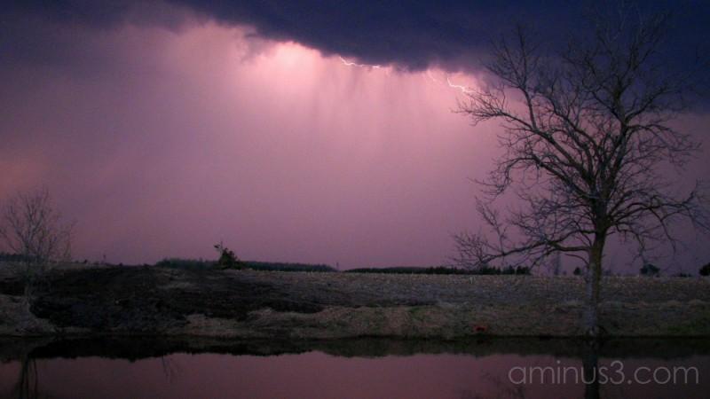 Lightning brightens a darkened sky.