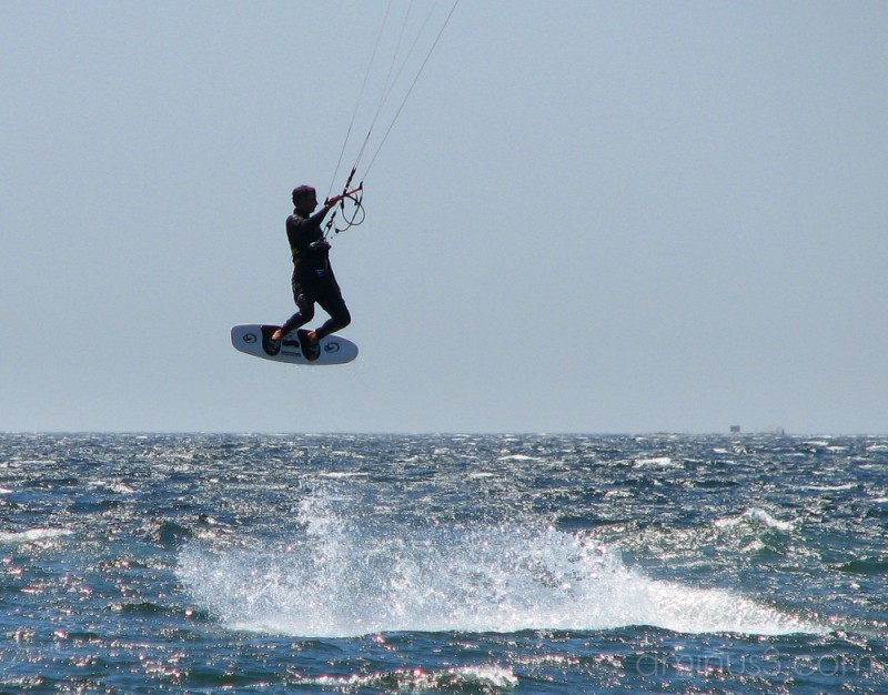 Kite surfer dangles in mid-air.