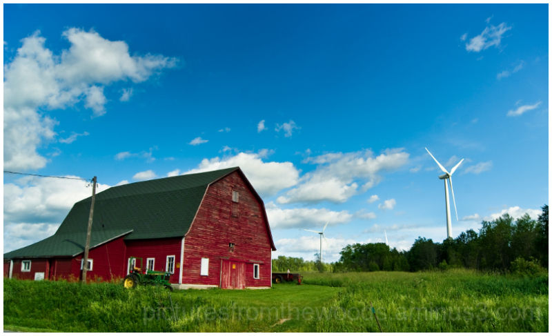 Old barn with backdrop of modern windmill.