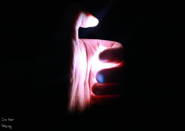 A torch lighting a hand