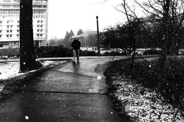 Girl walking through snow with an umbrella.
