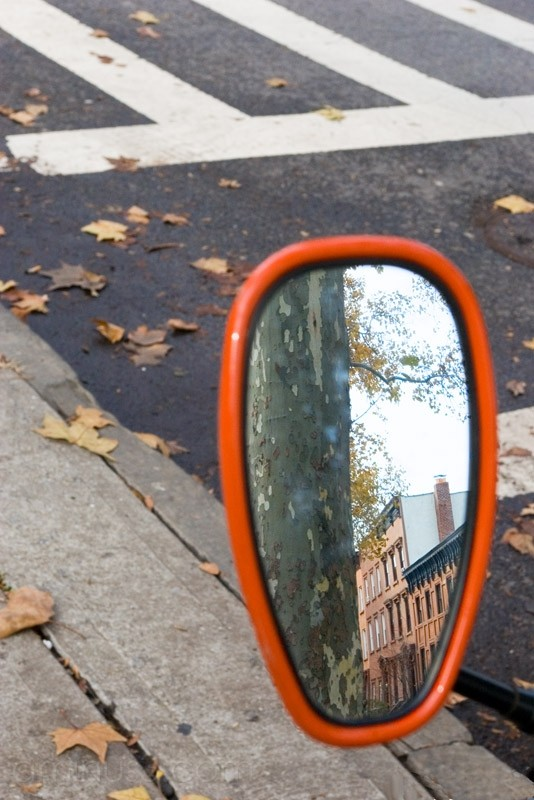 Brownstones reflected in motorcycle mirror