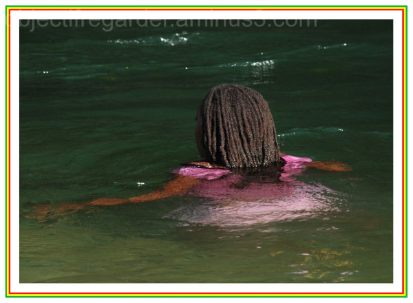 rasta girl bathing io the river in Dominica