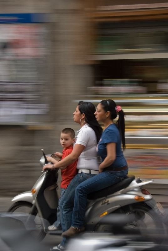 panned capture of family on a moto