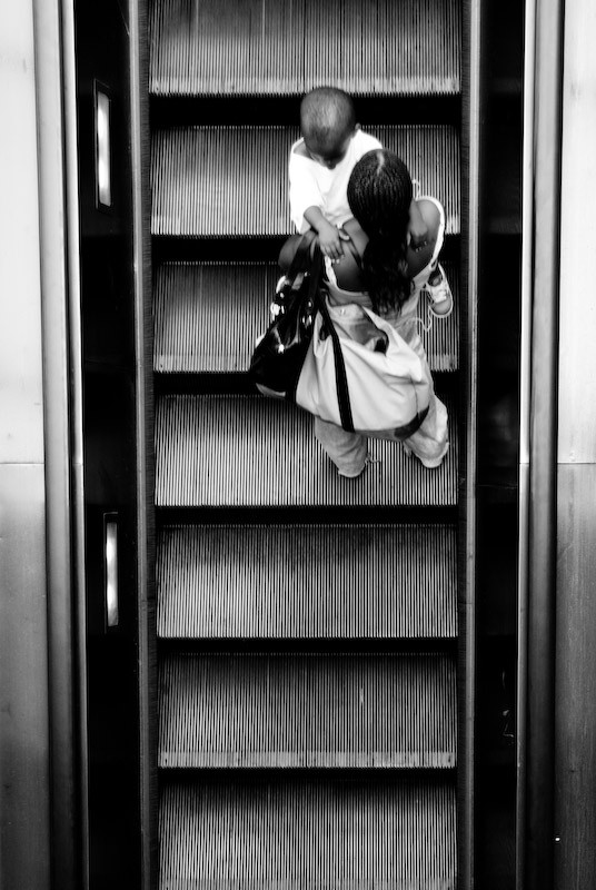 women and child riding escalator