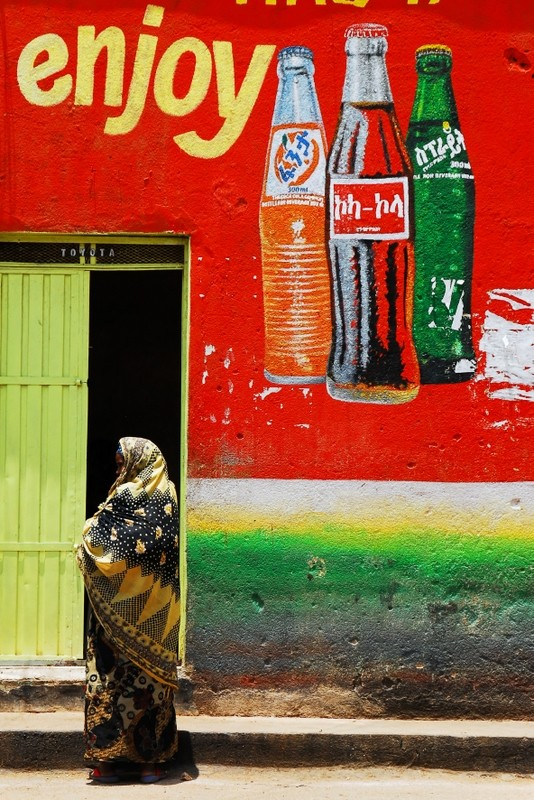 Woman standing in front of a Coca-cola ad, Harar